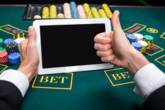 Casino, online gambling, technology and people concept. Close up of poker player with playing cards, tablet and chips at green casino table. first-person view stock photo