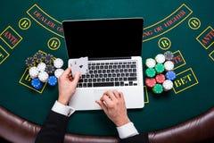 Casino, online het gokken, technologie en mensenconcept - sluit omhoog van pookspeler met speelkaarten Royalty-vrije Stock Foto