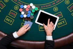 Casino, online het gokken, technologie en mensenconcept - sluit omhoog van pookspeler met speelkaarten Stock Foto's