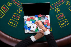 Casino, online het gokken, technologie en mensenconcept - sluit omhoog van pookspeler met speelkaarten Stock Fotografie