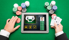 Casino player with cards, tablet pc and chips. Casino, online gambling, technology and people concept - close up of poker player hands with playing cards, tablet Stock Images