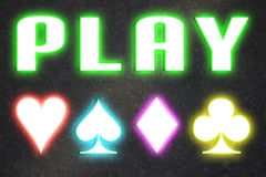 Casino playing games. Play word and cards playing symbols written with neon lights on casino wall Stock Images