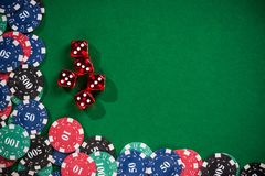 Casino poker chips and dices. On green cloth stock photography