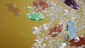 Casino poker chips falling in water close up stock video footage