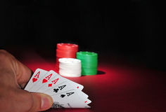 Casino poker chips. Five Aces. A man looks at his hand: five aces. He is a lucky guy! In the background are several stacks of casino chips of various heights and Stock Photo