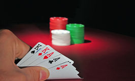 Casino poker chips. Full house. A man looks at his hand: Full house. In the background are several stacks of casino chips of various heights and colors. The Royalty Free Stock Photo