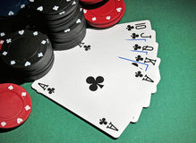 Casino poker chips with royal flush. Several stacks of casino chips of various heights and colors with a royal flush, all sitting on a green colored playing stock photography