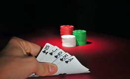 Casino poker chips Royal flush. A man looks at his hand: a royal flush. In the background are several stacks of casino chips of various heights and colors. The Stock Images