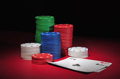 Casino poker chips two aces. Several stacks of casino chips of various heights and colors with two aces, a black and a red one, all sitting on a red colored royalty free stock photo