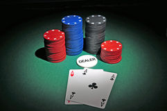 Casino poker chips  two aces. Several stacks of casino chips of various heights and colors with two aces, a black and a red one, all sitting on a green colored Royalty Free Stock Image