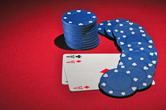Casino poker chips two aces. One stacks of casino chips with two ace, sitting on a red colored playing surface. The light in the scene is spot like Royalty Free Stock Photography