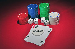 Casino poker chips two aces. Several stacks of casino chips of various heights and colors with two aces, a black and a red one, 4 dices and a dealer chips all Stock Photos