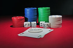 Casino poker chips two aces. Several stacks of casino chips of various heights and colors with two aces, a black and a red one, 4 dices and a dealer chips all Stock Image