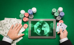 Casino poker player with cards, tablet and chips. Casino, online gambling, technology and people concept - close up of poker player holding playing cards, chips Royalty Free Stock Images
