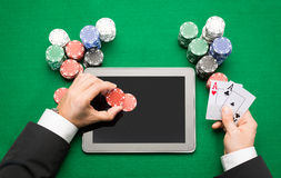 Casino poker player with cards, tablet and chips royalty free stock image