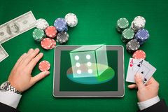 Casino poker player with cards, tablet and chips. Casino, online gambling, technology and people concept - close up of poker player with playing cards, tablet pc Royalty Free Stock Photo