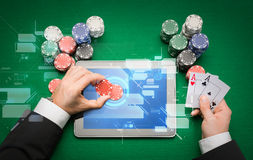 Casino poker player with cards, tablet and chips Stock Image