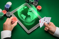 Casino poker player with cards, tablet and chips. Casino, online gambling, technology and people concept - close up of poker player with playing cards, tablet pc Stock Photo