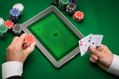 Casino poker player with cards, tablet and chips. Casino, online gambling, technology and people concept - close up of poker player with playing cards, tablet pc Stock Photography
