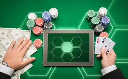 Casino poker player with cards, tablet and chips. Casino, online gambling, technology and people concept - close up of poker player with playing cards, tablet pc Royalty Free Stock Photography