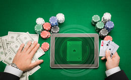 Casino poker player with cards, tablet and chips. Casino, online gambling, technology and people concept - close up of poker player with playing cards, tablet pc Royalty Free Stock Photos