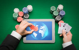 Casino poker player with cards, tablet and chips. Online casino, worldwide gambling, technology and people concept - close up of poker player with playing cards Royalty Free Stock Photography