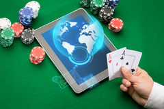 Casino poker player with cards, tablet and chips. Online casino, worldwide gambling, technology and people concept - close up of poker player with playing cards Stock Photography