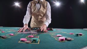 Casino professional croupier shuffles the poker cards and performing trick with cards. Black background. Bright light. Casino professional croupier shuffles the stock footage