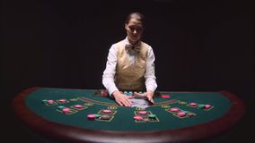 Casino professional dealer shuffles the poker cards and performing trick with cards. Black background. Slow motion. Casino professional dealer shuffles the poker stock video