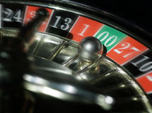 Casino roulette wheel. Close up of a ball landing on a casino roulette wheel table on zero stock photography
