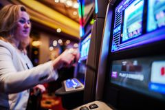 Casino Slot Games Play. Caucasian Woman in Her 30s Playing Slot Machine in the Casino Stock Photos