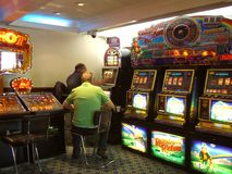In the casino. Slot machines and some people gambling in the casino Royalty Free Stock Image