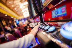 Casino Slot Video Games. Woman Playing Video Slot in the Casino. Hand on Betting Button Closeup Photo stock image
