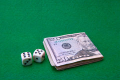 Casino table with Dollar notes and dice Royalty Free Stock Images
