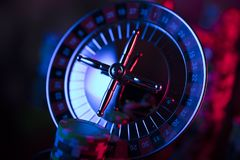 Gambling theme. Place for typography. Casino theme. Roulette wheel and stack of chips on color bokeh background. Place for text royalty free stock image