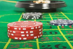 Casino tokens and roulette - focus on red tokens Royalty Free Stock Images