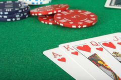 Casino tokens and a royal flush over green Stock Image