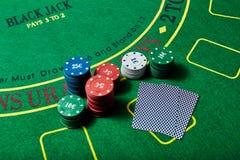 Casinospaanders en dek van kaarten die op casinolijst liggen Royalty-vrije Stock Afbeelding