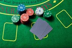 Casinospaanders en dek van kaarten die op casinolijst liggen Stock Afbeeldingen
