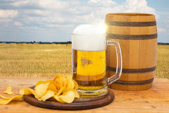 Cask beer and chips on the background. Cask beer and chips on the background of the countryside Royalty Free Stock Image
