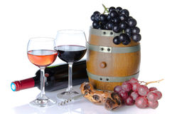 Cask, bottle and glasses of wine with red and black grapes Royalty Free Stock Photography
