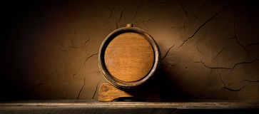 Cask near wall. Wooden cask near clay wall in cellar Stock Photo