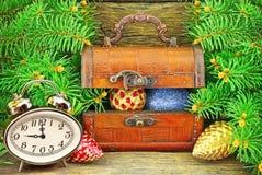 Casket med gåvor, klockor, julleksaker, nära träd för nytt år. Royaltyfri Foto