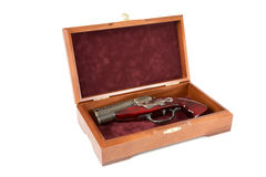Casket with a toy pistol Royalty Free Stock Image