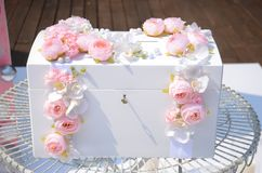 Casket for a wedding for gifts. Luxurious white wooden box decorated with pink flowers. Casket for a wedding for gifts royalty free stock photography