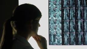 Caso raro de ferimento espinal, doutor que olha o raio X do paciente, fazendo o diagnóstico filme
