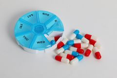 Caspules and a pillbox for a week. Colorful capsules with a round pillbox are lying in the white studio stock photos