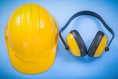Casque antichoc de bouche-oreilles de sécurité sur le concept bleu de construction de fond Photographie stock libre de droits