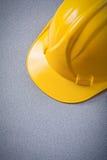 Casque antichoc de sécurité jaune sur le concept gris de construction de fond Photo libre de droits