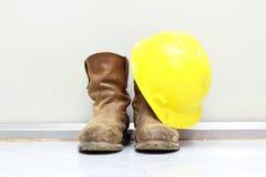Casque antichoc et bottes jaunes Photographie stock libre de droits